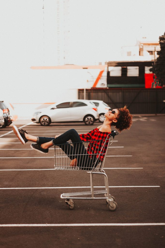 lady wearing vintage clothing smiling in a shopping trolley